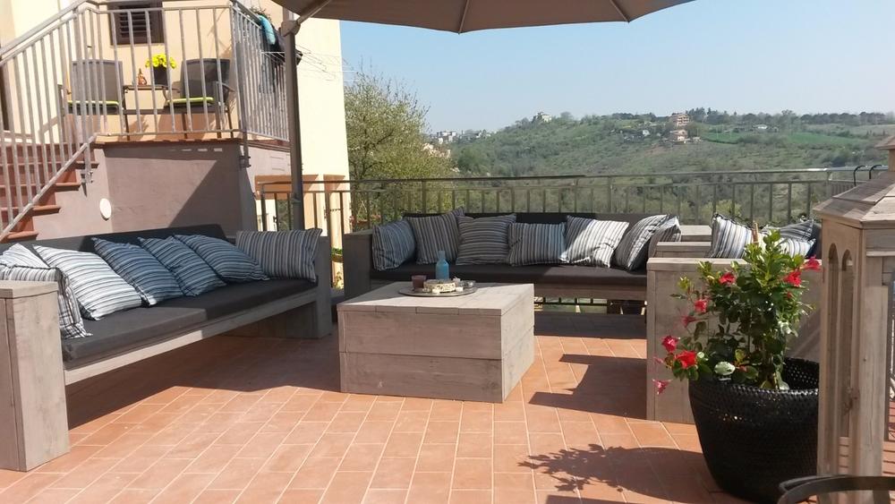 Steigerhout loungeset met kussens op een terras in italie met mooi uitzicht