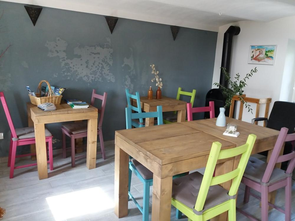 Steigerhout tafels in ontbijtruimte b&b met gekleurde stoelen