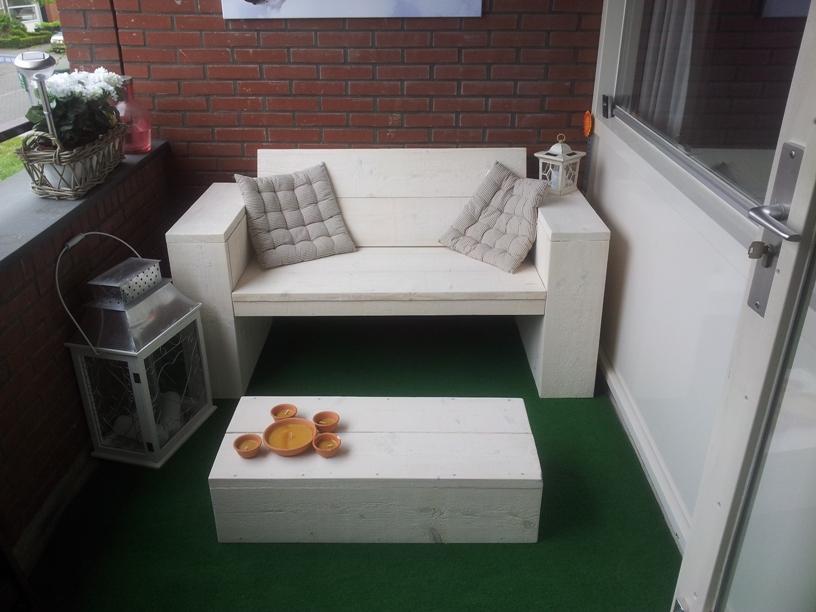 Kleine loungebank steigerhout op een balkon